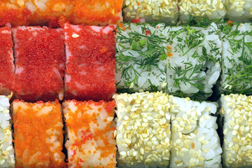Sushi rolls with ingredients as background closeup