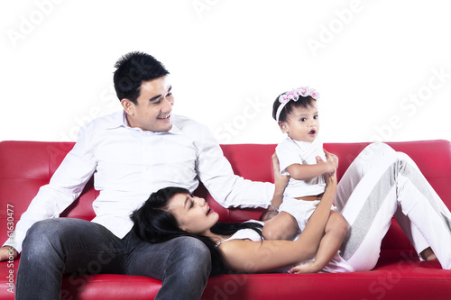 Happy asian family playing on sofa