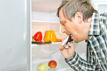 Mann am Kühlschrank mit Schokoladentafel