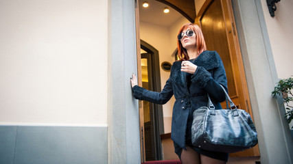 Young elegant woman in front of hotel.