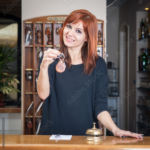 Young smiling attendant at hotel reception offering the key of t