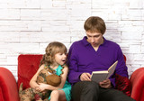 father and little daughter reading