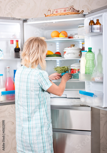 Young mother with a child takes food out of the fridge.