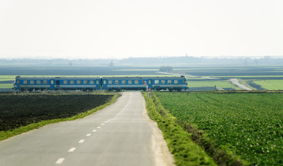 Blue train crossing over rural road