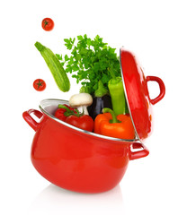 Colorful vegetables coming out of a red cooking pot