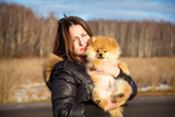 Beautiful girl holding a dog Spitz. Small breeds.