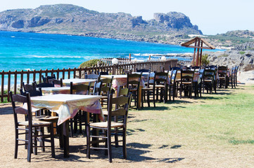 Table and chairs of a Greek taverna on the sea coast