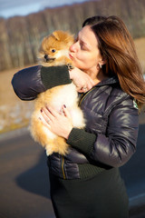 Young attractive girl kissing puppy spitz dog with love.