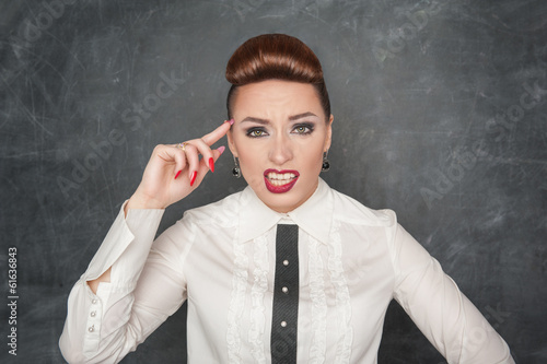 Woman gesturing with finger to her head