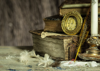 Old books, antique clock, candle and quill. Vintage postcard.