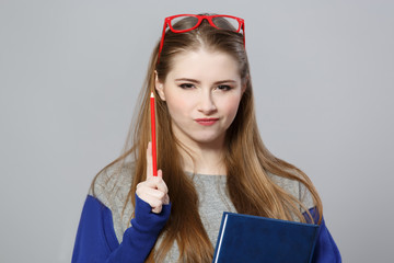 Girl holds pencil and notebook