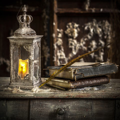Vintage lamp for the candle and old books on wooden table