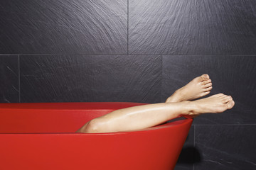 Female legs in a red bathtub