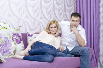 A happy young couple in jeans sitting on the couch
