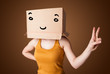 Young woman gesturing with a cardboard box on her head with smil