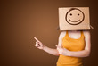 Young girl gesturing with a cardboard box on her head with smile