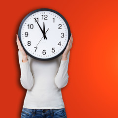 Woman holding a clock over face against orange background