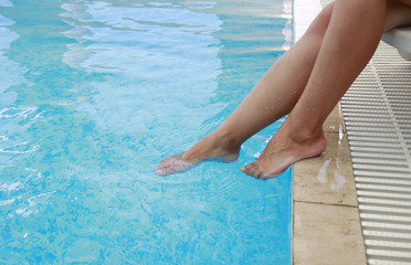 female legs in the water pool