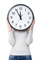 Woman holding a clock over face isolated on a white background