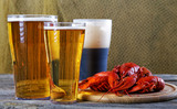 Tasty boiled crayfishes and beer on old table