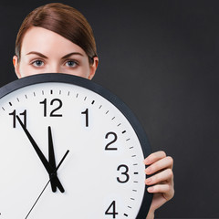 Young woman holding a big clock against chalkboard background