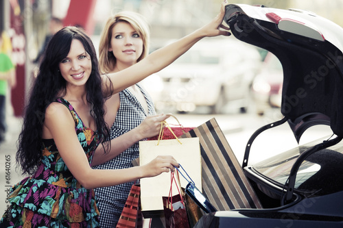Two young women with shopping bags on the car parking