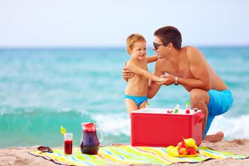 family having fun on beach picnic