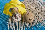 Easter background with quail eggs and ribbons