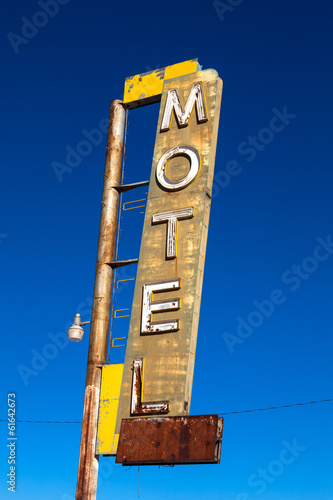 Vintage, neon, decrepit motel sign with a sky background