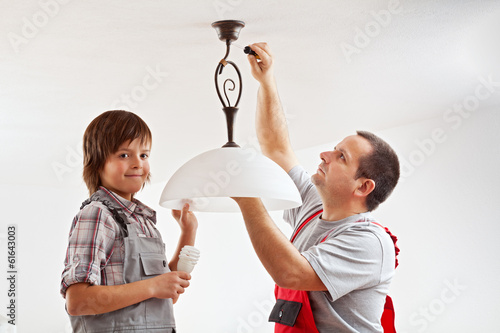 Father and son installing a ceiling lamp