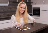 Young woman using a tablet pc in the kitchen with coffee