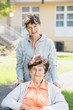 Pflegerin Tochter fährt Mutter, Seniorin im Rollstuhl