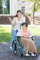 junge Pflegerin fährt mit Seniorin spazieren im Rollstuhl