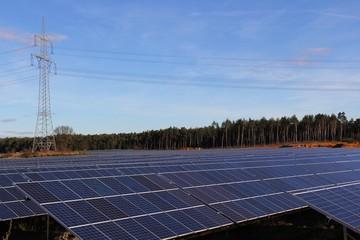 Solarfeld vor Strommast und Wald