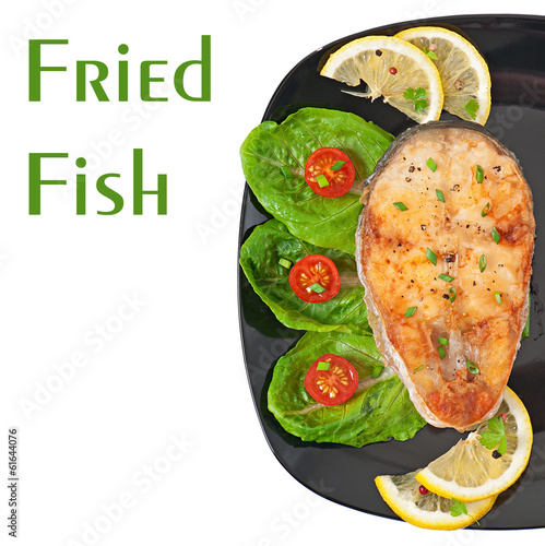 Fish dish- fried fish fillet with vegetables on white background
