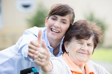 lachende Frau mit seniorin Daumen hoch