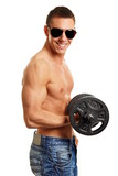 Young athletic man in sunglasses holds dumbbell and exercises