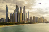 Skyline in Dubai Marina at Jumeirah Beach with Airplane