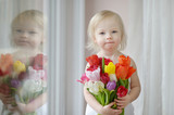 Adorable toddler girl with tulips by the window