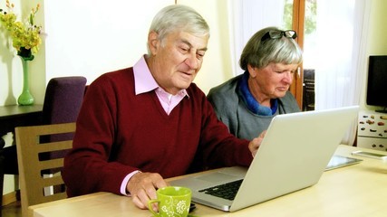 Senior couple kissing while working with technology