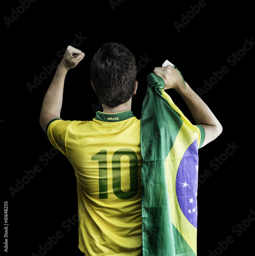 Brazilian soccer player holding the flag of Brazil celebrates