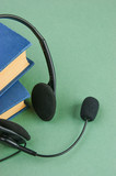 Headphones with a microphone and a stack of books on a green bac