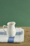 White jug and dishcloth on old wooden table over green backgroun