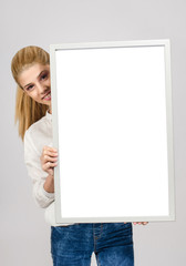 Young blonde student girl smiling holding a white blank board.