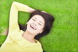 smiling  woman listening music and lying on a meadow