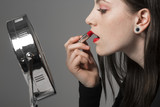 Young Woman Applies Red Lipstick in Makeup Mirror