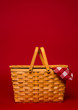 A wicker picnic basket with red gingham tablecloth on a red back - 61653606