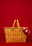A wicker picnic basket with red gingham tablecloth on a red back
