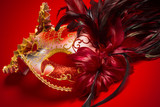 A red, gold and black mardi gras mask on a red background