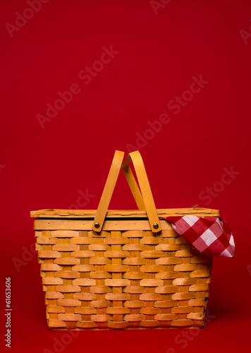 In de dag Picknick A wicker picnic basket with red gingham tablecloth on a red back